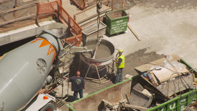 A rotating cement mixer pours wet cement into a large bucket during construction of the new World Trade Center in summer 2011, Manhattan, New York City, USA.