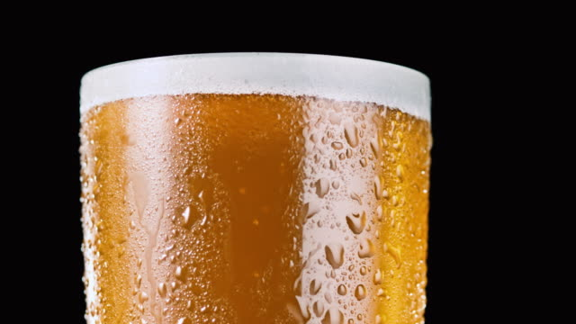 rotating close-up view of a golden beer with foam - pint glass stock videos & royalty-free footage