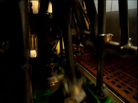 Rotating crank shaft and oscillating pistons in engine room of steam boat