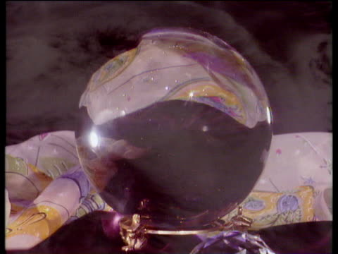Rotating crystal ball on stand with swirling mist