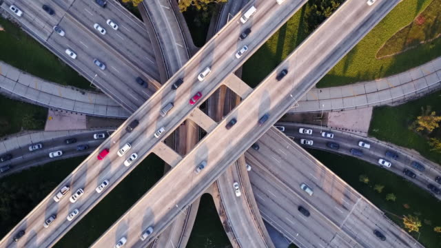 rotating drone shot of freeway interchange - mezzo di trasporto video stock e b–roll