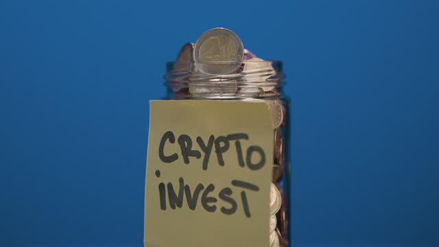 青い背景に暗号投資テキストと貼り付けられた接着剤ノートと小銭と2ユーロ硬貨で完全な回転ガラス瓶 - イーサリアム点の映像素材/bロール