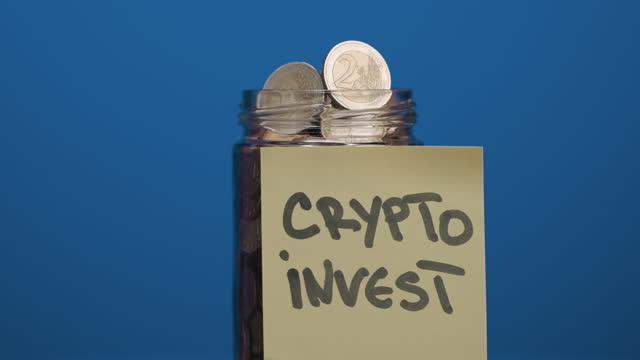 青い背景、スローモーションに暗号投資テキストと貼り付けられた接着剤ノートとペニーと2ユーロ硬貨で完全な回転ガラス瓶 - イーサリアム点の映像素材/bロール