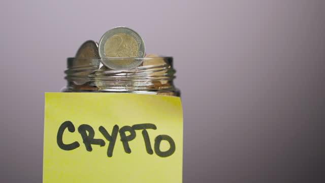 stockvideo's en b-roll-footage met roterende glazen pot vol met centen en twee euromunten met geplakte kleefnoot met cryptotekst erop, grijze achtergrond - mining
