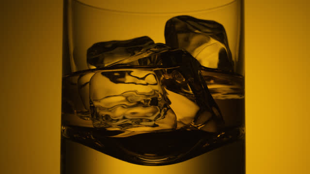 rotating glass of whisky with ice cubes - vignette stock videos & royalty-free footage