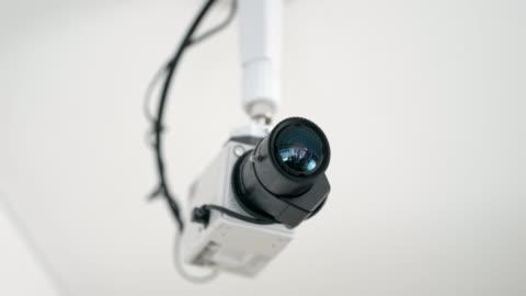 ds roterande skott av en säkerhetskameran monteras på ett tak - övervakningskamera bildbanksvideor och videomaterial från bakom kulisserna