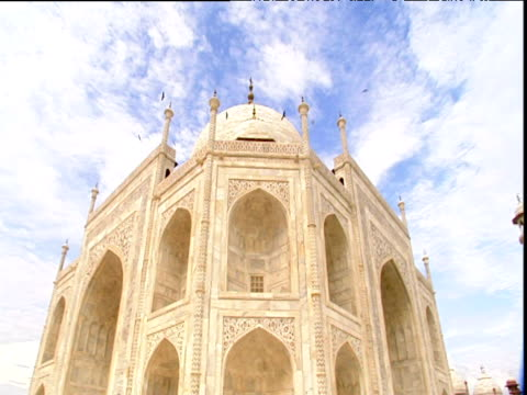 rotating shot of corner of taj mahal under cloud dotted sky birds hovering in distance agra - agra video stock e b–roll