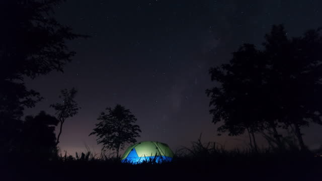 Rotating stars above tent at night. Time lapse