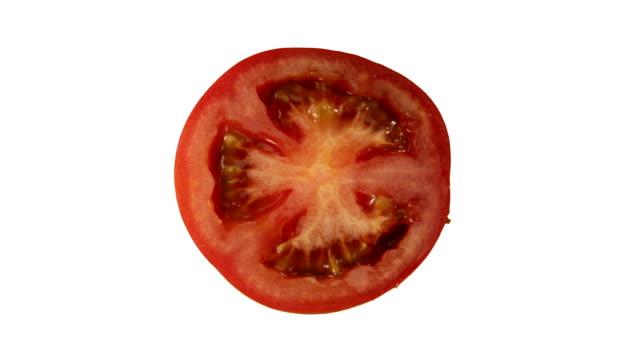 rotating tomato slice on white ground - slice stock videos & royalty-free footage