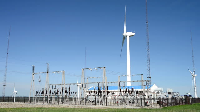 rotating wind turbine and transformer sets under blue sky,real time. - transformer stock videos & royalty-free footage
