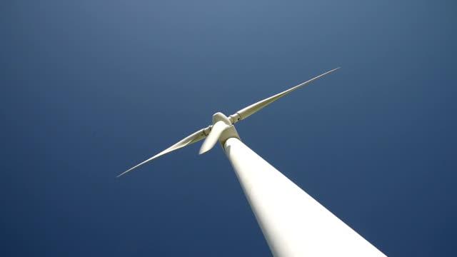 vídeos y material grabado en eventos de stock de giratorio de la turbina de viento en el cielo azul, tiempo real.   - vista de ángulo bajo