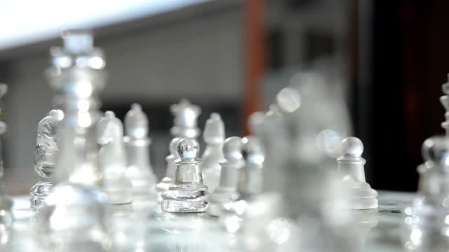 vidéos et rushes de rotation: un pion parmi verre d'échecs est à l'origine sur la fenêtre - verre translucide