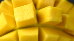 Rotation close-up of rip mango slice cubes cut in 4K resolution