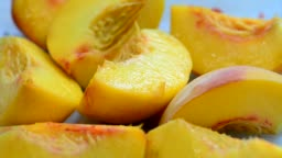 Rotation of a plate with slices of ripe juicy peach on the table, video, soft focus