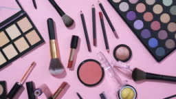 Rotation of cosmetic and make up brush collection on pink background