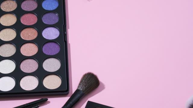 コピースペースとピンクの背景を持つ化粧品とメイクアップブラシコレクションの回転 - メイクアップブラシ点の映像素材/bロール