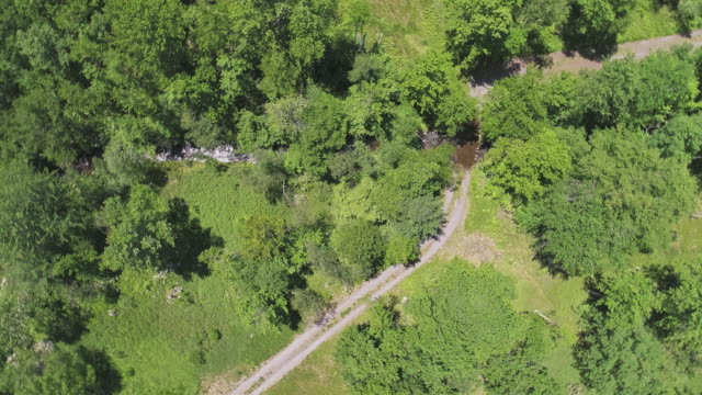 Rotation. The aerial drone directly above view to the country road and the small river in the forest in the Pocono Mountains at the summer sunny day.