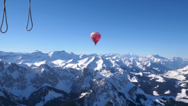 rougemont, switzerland -  03 21 2019:   a hot air balloon in flight over the snow covered high mountain alpine peaks of central switzerland. - polarklima stock-videos und b-roll-filmmaterial