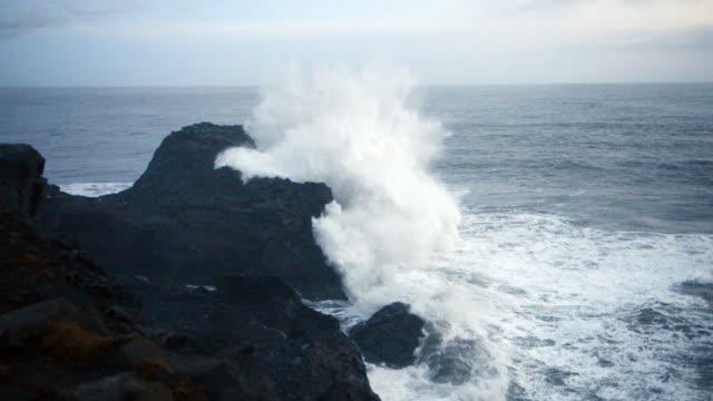 rough atlantic ocean waves crashing on rocky coastline in dyrholaey iceland - dyrholaey stock videos & royalty-free footage