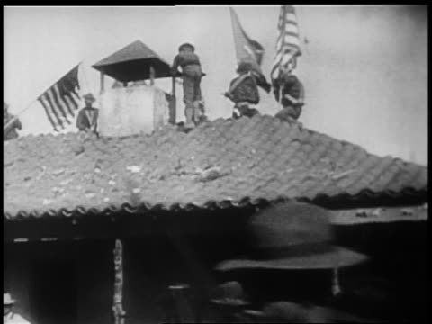 Rough Riders on tile roof of building raising US flags / SpanishAmerican war