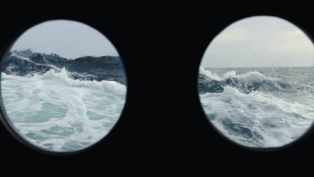 vidéos et rushes de mer rugueuse d'un bateau à voile - hublot