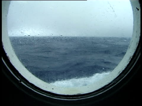 rough sea from ship's porthole, drake passage, antarctica - drake passage stock videos and b-roll footage