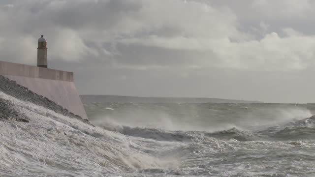 Rough, stormy sea with large waves breaking against sea wall topped by lighthouse, Porthcawl, Wales