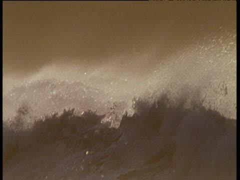 rough surf and spray on stormy coast, orange light, ireland - traumartig stock-videos und b-roll-filmmaterial