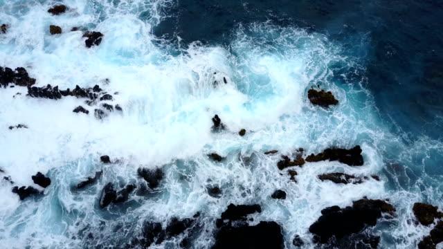 Rough Surf Crashing Among Rocks Below Drone