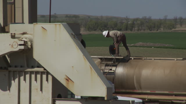 A roughneck collects oil from an oil head at Bakken Oil Field in Tioga, North Dakota.