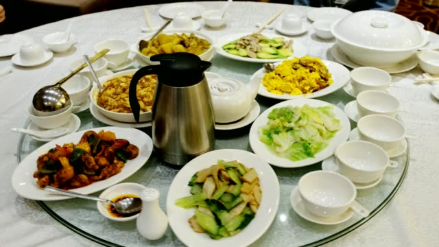 round glass table rotating with chinese food, meat and tea with family in restaurant - bowl stock videos & royalty-free footage