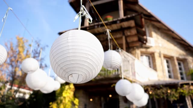 round paper lantern in back yard of beautiful house - stone house stock videos & royalty-free footage