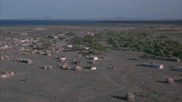 vídeos de stock e filmes b-roll de round, thatched huts and low buildings dot the dry african plains. - planície