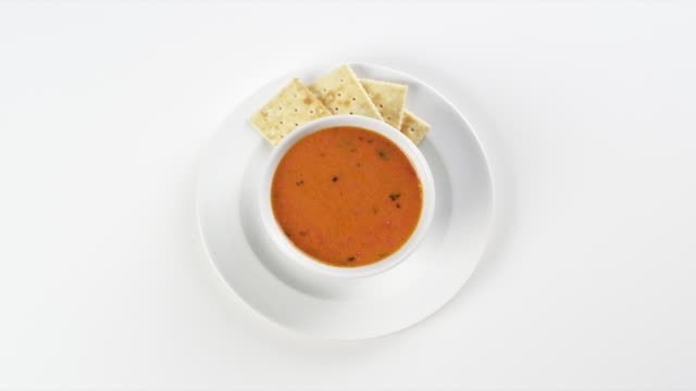 cu round white plate with colorful red tomato soup bisque and crackers / omaha, nebraska, united states - tomato soup stock videos and b-roll footage