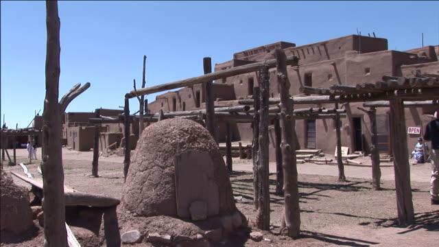 a rounded rock formation rests next to a rickety pole structure in taos pueblo. - adobe bildbanksvideor och videomaterial från bakom kulisserna
