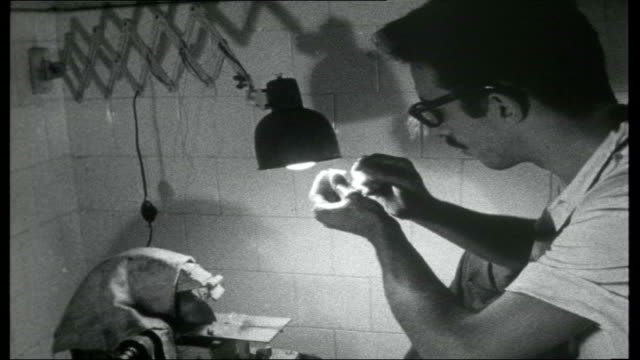 a day in rio int men cutting semiprecious stones in jewellers' workshop / man cutting aquamarine with diamond saw then holding cut stone up to light... - 1950 1959 stock videos & royalty-free footage