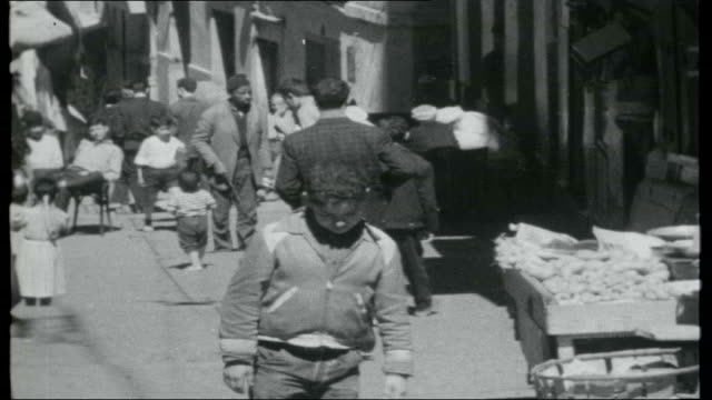 algeria algeria algiers ext narrow street in city centre trader along carrying tray of buns on his shoulder gv people along in street man hand sewing... - アルジェリア点の映像素材/bロール