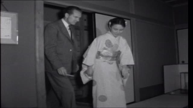 vidéos et rushes de anniversary in tokyo; ext car pulling up outside buddhist temple and reporter enters reporter greeted by two geisha girls int reporter enters... - geisha