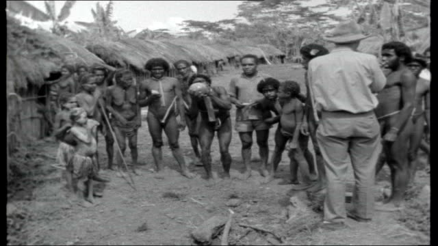 back of beyond; papua new guinea: ext close up new guinea tribesman / tribeswoman / group of stone age villlagers opening credits air view jungle - new age stock videos & royalty-free footage