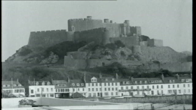 Boom Island CHANNEL ISLANDS Jersey Gorey EXT Gorey Castle on top of hill with houses along waterfront below Reporter to camera