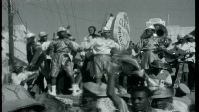 castro's neighbour haiti mardi gras celebrations including local man in hat and beads mass of dancing crowds moving to drums at festival playing... - gras stock videos and b-roll footage