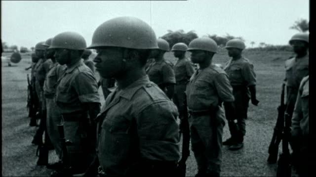 Congo Countdown Kwilu Province Kikwit 'Kikwit' sign on airport building Soldier saluting as Mobutu descends plane steps Mobutu speaking to Congolese...