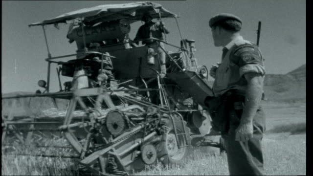 vidéos et rushes de cyprus a general returns / calcutta combine harvester harvesting in field with greek cypriot farm workers frenchcanadian un soldiers supervise the... - invisible