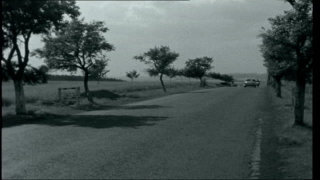 Czechoslovakia Today Location unknown Motorcycle and car away down otherwise empty country road / Families in summer clothing walking down country...