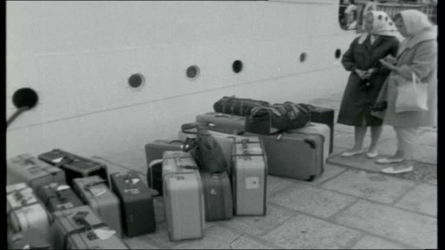 dalmatian journey titles yugoslavia dubrovnik ext variious shots of ferry at quayside and tourists departing suitcases on quayside vox pops two... - 旧ユーゴスラビア点の映像素材/bロール