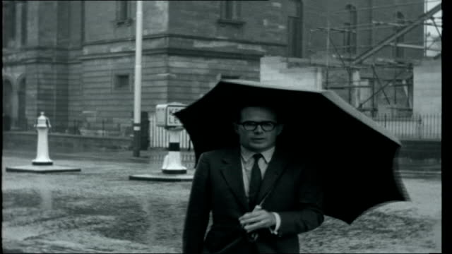 day of rest; scotland: greenock: ext opening titles seen over church steeples as church bells ring reporter john whale holding umbrella and speaking... - 黒猫点の映像素材/bロール