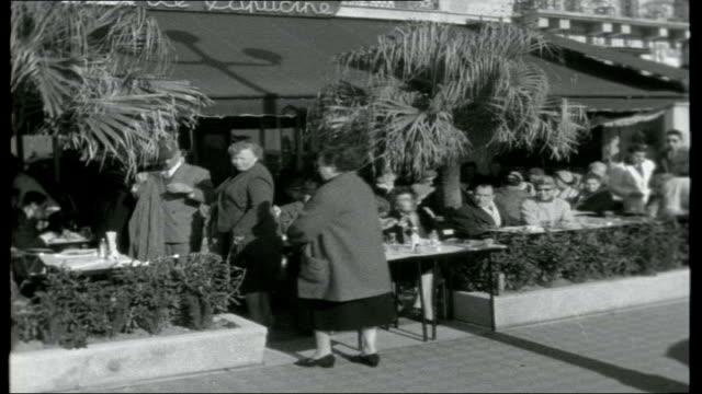 do the french like us?; france: cannes: ext b/w man standing by sea at holiday resort feeding bread to seagulls / luxury yachts and boats moored at... - 1950 1959 stock-videos und b-roll-filmmaterial