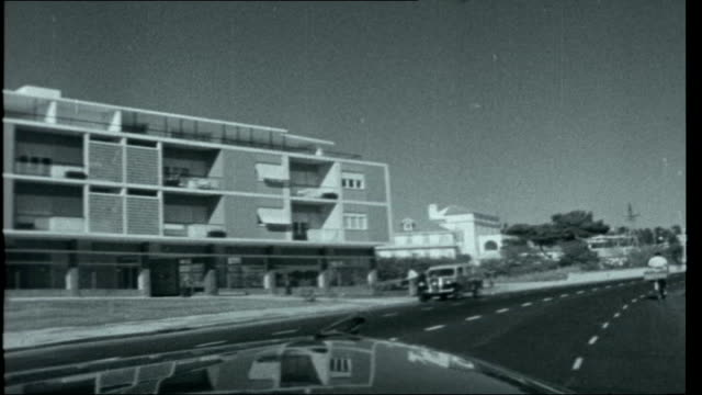 estoril establishment; ext travelling shots from car as along estoril seafront past buildings and beach estoril beach scene with ends titles overlaid - エストリル点の映像素材/bロール