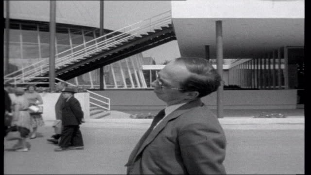 expo 58; brussels: reporter along as arriving at exhibition: policeman directing traffic coaches arriving policeman directing people reporter... - moving up点の映像素材/bロール