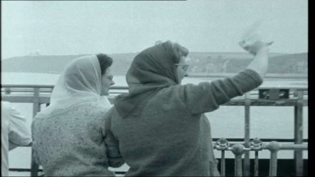 vidéos et rushes de first time abroad; opening credit sequence england: folkestone: ext various views of girls in 1960s dresses and bouffant hair walking up gangplank... - prêtre